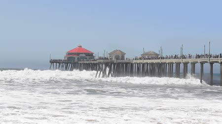 laranja : Post storm surge at the Huntington Beach pier shows the formation of waves crashing against the pier's pilings and creating turbulent surf. Stock Footage
