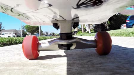 skate : A camera is mounted under a skateboard while a rider moves along a sidewalk. Stock Footage