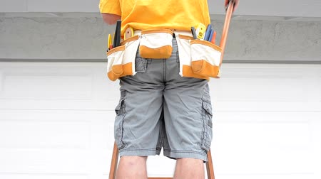 preparado : A contractor standing on a ladder pulls a hammer from his tool belt then places it back in its harness.
