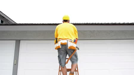осмотр : A contractor wearing a tool belt climbs a ladder and conducts a quick roof assessment on a residential home during an overcast day.