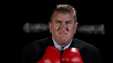 kulaklar : An angry, middle-aged businessman wearing boxing gloves shoots steam from his ears as he becomes more irritated. Stok Video