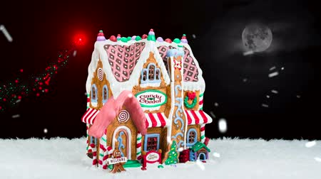 mézeskalács : A gingerbread house during a snowy Christmas shows Santa's sleigh off in the distance forming a red and green holiday sparkle trail