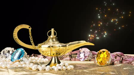 The formation of a magical deity from a gold, magic lamp surrounded by a wealth of jewelry and fantasy isolated on black
