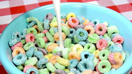 cereais : Pouring milk into a bowl of sugary, fruity cereal during breakfast