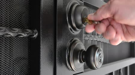 cadarço : A man unlocks a security door that is set up with a deadbolt and door knob lock system.