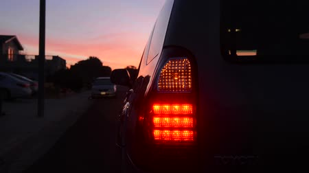 światło : A car blinker and taillight at night used for safety and signaling for turns.