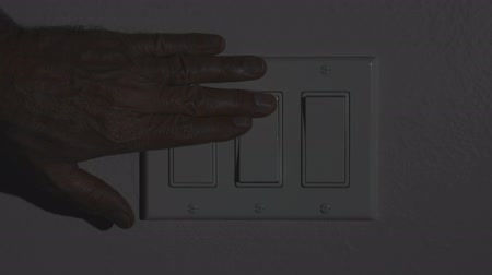 comutar : A man turns on a hallway light then a main living room light, bringing darkness to light. Stock Footage