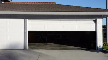 drzwi : A roll up garage door on a residential home closing during the daytime