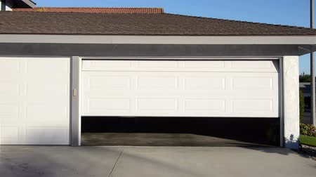 garagem : A roll up garage door on a residential home opening up during the daytime Vídeos