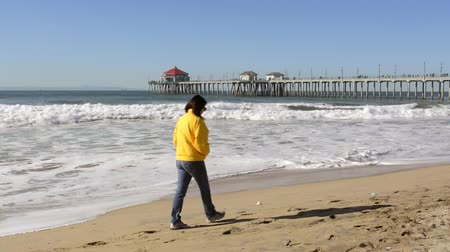 laranja : A woman walks along the shoreline at historic Huntington Beach pier in Orange County California during a cold, windy day. Stock Footage