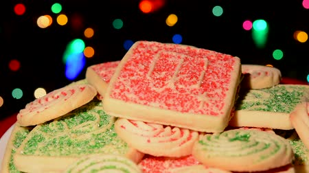 keksz : Close up of a plate of sweet holiday cookies in front of a Christmas tree with colorful, blinking lights