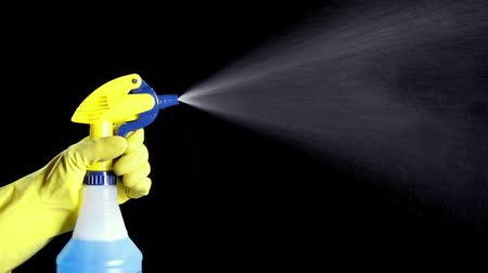 pulverização : A person uses a hand held pump sprayer and protective glove to spray cleaning chemicals.