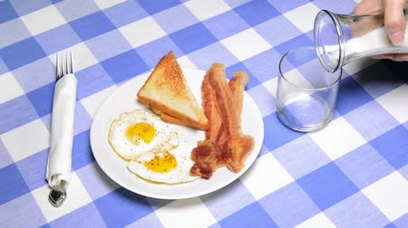 бекон : A breakfast diner setting with eggs, bacon, toast and ice cold milk set on a classic blue and white checkered tablecloth.