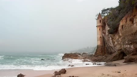 laranja : An early morning, hazy day video of the famous La Tour tower in Laguna Beach, California.  The tower, built in 1926, used to be a stairway for the wealthy living on the Cliffside but is not a landmark site for adventurous tourists and locals.