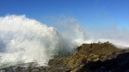 fala : Powerful waves shown in slow motion and regular speed crash against an ocean reef sending seawater into the air and over the rugged terrain