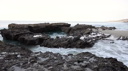 crevice : Wide pan of an ocean reef crevice receives a powerful wave of water causing a big break against the reef. Stock Footage