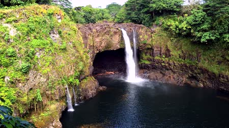 waterfall cascading into pool : Time lapse of Rainbow Falls in Hilo Hawaii forms cascading flows into a natural pool and often casts colorful rainbows when the sun position is just right