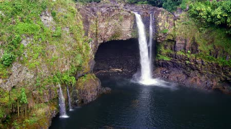 waterfall cascading into pool : Beautiful Rainbow Falls in Hilo Hawaii forms cascading flows into a natural pool and often casts colorful rainbows when the sun position is just right, as shown here.