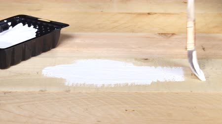 brushing : A painter brushes paint primer onto raw wood in preparation for a final top coat of another color.