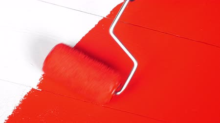 tintas : A painter uses a roller to apply a topcoat of red paint to a white, primed wood surface.