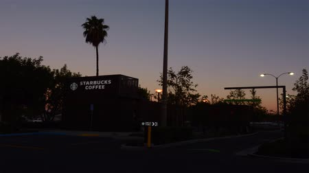 franczyza : ORANGE COUNTY, UNITED STATES, OCTOBER 2015: Customers arriving at a Starbucks coffee drive through during dawn as the sun rises Wideo