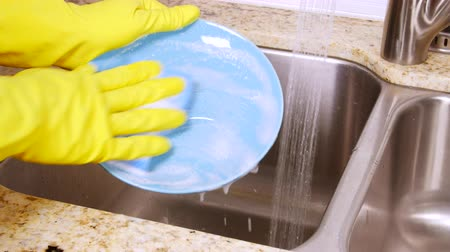 sıkıcı iş : A person washes dinner plates using soapy detergent, a sponge and protective gloves then rinses them before drying Stok Video