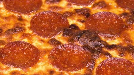 kapatmak : Close up of a freshly baked pizza with delicious pepperoni, cheese, and marinara sauce ready to eat.