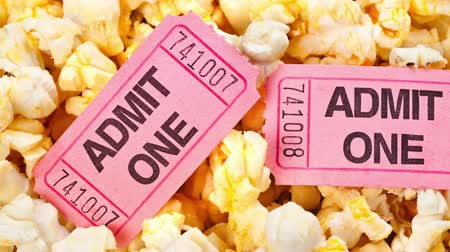 filmes : Motion over the top of a tub of fresh, hot popcorn with pink movie tickets for admission into the theater. Stock Footage