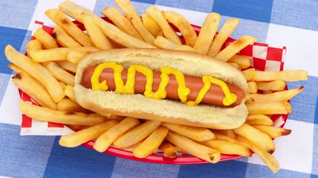 картофель фри : A freshly barbecued hotdog with traditional yellow mustard surrounded with French fries served in a classic red basket.