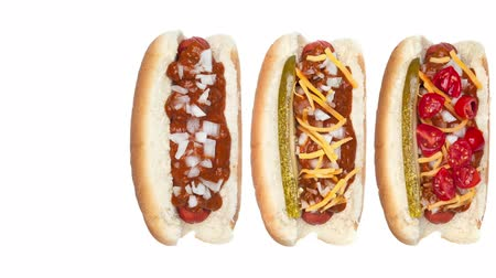 condimento : An assortment of various hotdogs with a selection of condiments and toppings from chili and cheese to tomatoes and relish.
