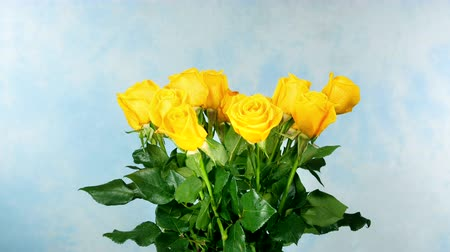 Роуз : A classic bouquet of yellow roses rotating against a blue background.