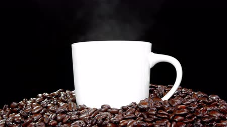 núpcias : Freshly roasted Columbian coffee beans surround a steaming, hot cup of coffee. Stock Footage
