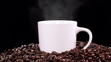 xícara de café : Freshly roasted Columbian coffee beans surround a steaming, hot cup of coffee. Vídeos