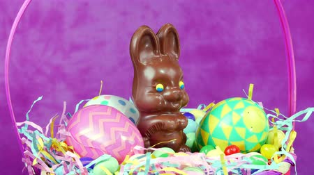 nyuszi : A chocolate Easter bunny rotating in a decorated basket with candy and decorative eggs framed against a pink, festive background.