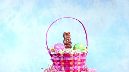 nyuszi : A chocolate Easter bunny rotating in a decorated basket with candy and decorative eggs framed against a blue, festive background. Stock mozgókép