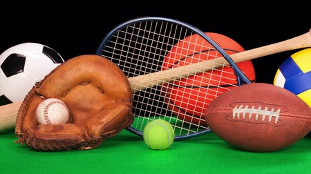 serpenyő : Pan of sports equipment including a basketball, baseball gear, a tennis racquet, soccer ball and volleyball against a black background. Stock mozgókép