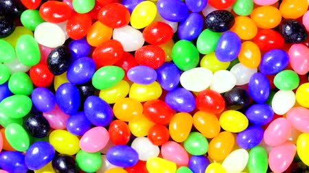 besinler : Rotating bowl of colorful Easter jellybeans for use as a seasonal background for placement of copy. Stok Video