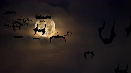 dia das bruxas : Halloween setting with animated bats flying across a spooky moon and dark amber sky highlighted by fog and clouds.  Can be used as a design element for placement of copy and Halloween messaging.