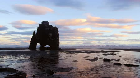 beautifully : Dinosaur Rock along a beach in Iceland during a morning sunrise reflects beautifully against a cold ocean shoreline