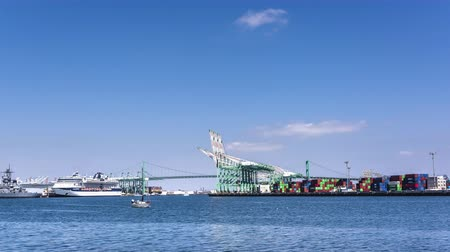 navigasyon : An empty oil tanker is being navigated out of Long beach harbor by two powerful tugboats during a sunny day