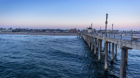 Time lapse at the Huntington Beach Pier in California shows the non-stop hustle and bustle of tourist traffic as day becomes night and the local pier and city lights brighten to give a festive effect to the ocean landmark.