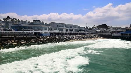 During a bright, sunny day ocean waves gently rush to shore in a small waterfront town along the coast of Redondo Beach