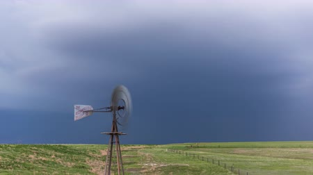 A windmill moves to the flow of the wind as bursts of lightning illuminate the sky