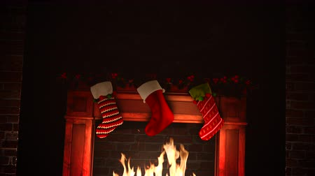 şömine : An animated fire in a fireplace subtly flickers with Christmas stockings hanging over the joyous warm flames. Stok Video