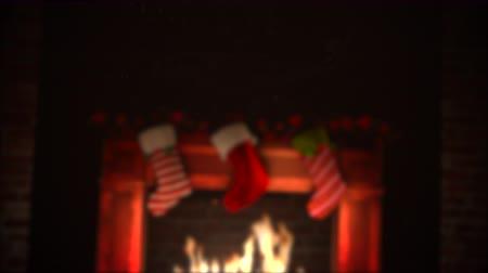 An animated fire in a fireplace subtly flickers with Christmas stockings hanging over the joyous warm flames. Stok Video
