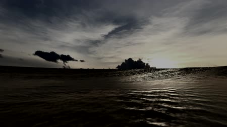 Animated video shows a sunset over a tropical island and sunlight glistening off the surface of the ocean surface at dusk. Stok Video