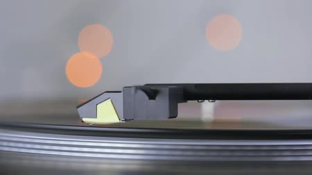 Close up of modern record player arm and needle playing a vinyl record with bokeh lights