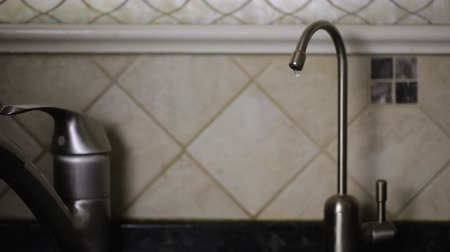 Water dripping from a modern faucet kitchen sink