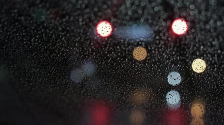 Raindrops on windshield and bokeh cars lights Стоковые видеозаписи