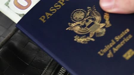 passaporti : A mans hand placing a United States of America passport with 100 dollar bills in it on a packed bag or luggage in preparation for a trip